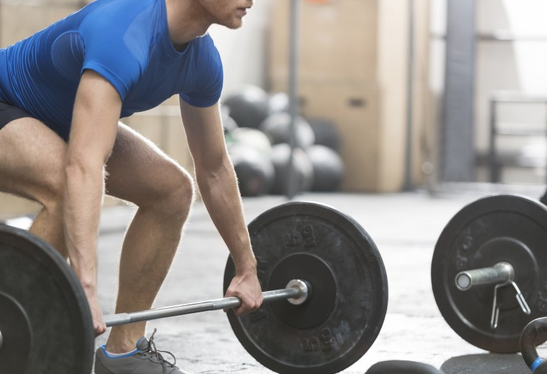 Low section of dedicated man lifting barbell in crossfit gym