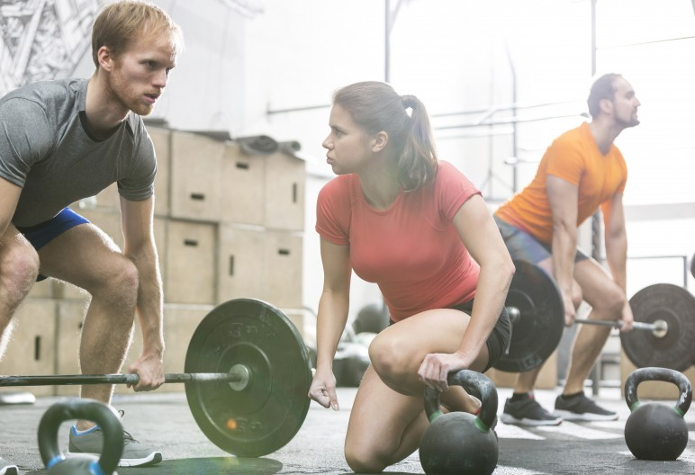People weightlifting in crossfit gym
