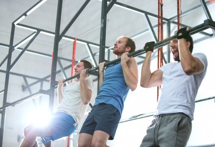 Low angle view of dedicated men doing chin-ups in crossfit gym