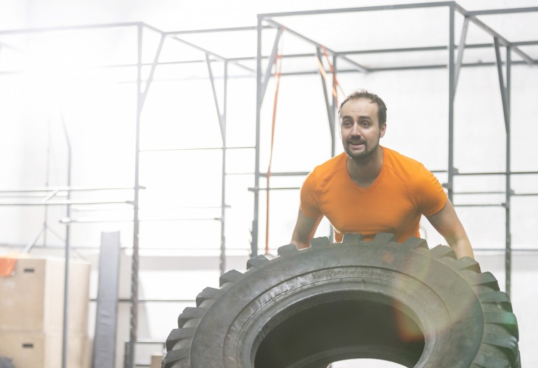 Dedicated man flipping tire in crossfit gym